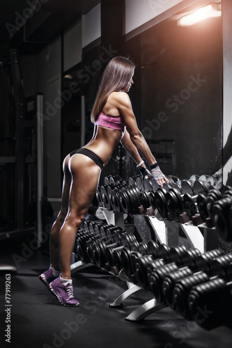 canvas print picture Sexy athlete with a dumbbell in the gym lean on dumbbell row