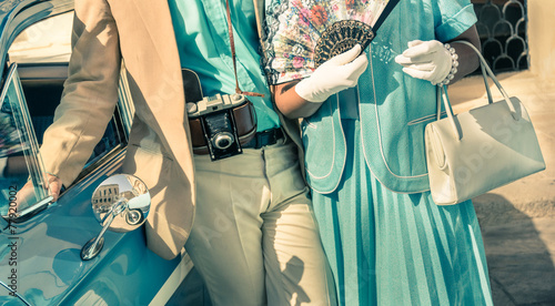 Vintage couple posing with retro clothes next to classic car - 77920002