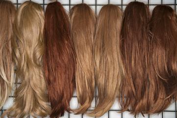 Verschieden farbige Perücken für Frauen aneinander gereiht
