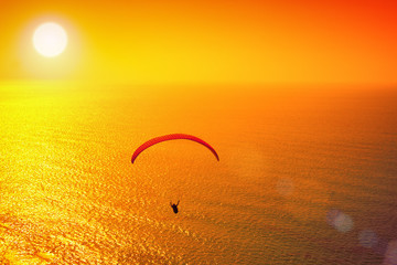 Silhouette of paraglider soaring over sea at sunset