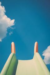 Kinderrutsche vor blauem Himmel mit Wolken