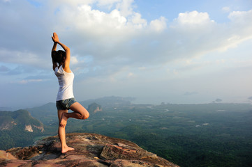 yoga woman at on mountain peak rock