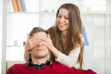 Woman puts his hand over his eyes a man to make him a surprise