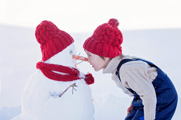 Happy beautiful child building snowman in garden,nose to nose