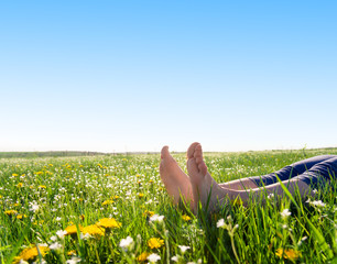 bare feet on spring grass and flowers