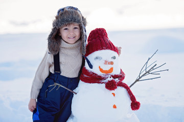 Happy beautiful child building snowman in garden