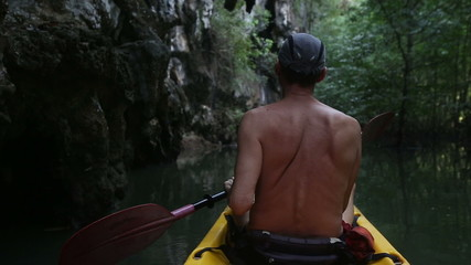elder tanned man floating on kayak along the river near the clif