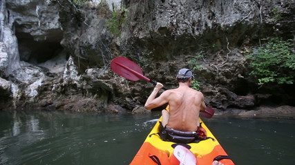 man floating on kayak along the lagoon turns his canoe around