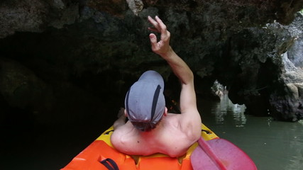 elder tanned man floating in canoe through the rocky grotto