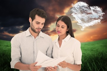 Composite image of attractive young couple reading their bills