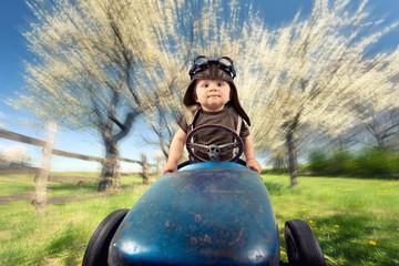 Kind mit Tretauto auf Frühlingswiese