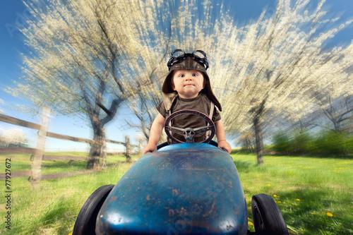 Leinwanddruck Bild Kind mit Tretauto auf Frühlingswiese