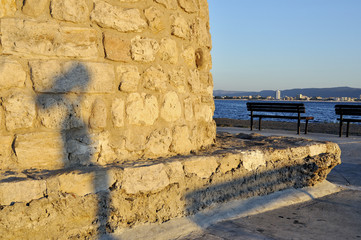 Shadow of street telescope on embankment of the sea