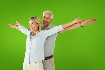 Composite image of happy couple standing with arms outstretched