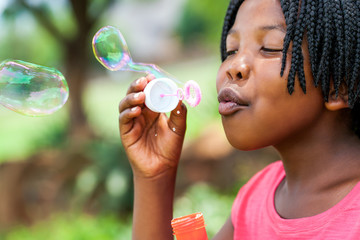 African girl with braids blowing bubbles.