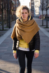 Young blond girl walking in the street
