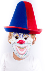 Smiling little boy masked as a clown