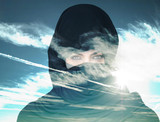 Double exposure of woman wearing burqa and cloudscape