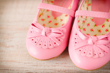 Detail of a pink girl shoes over wooden deck floor.