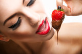 Fototapety Seduction - red female lips eating chocolate strawberries