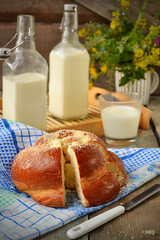 Bun with butter and milk. Breakfast in rustic style. Selective f