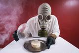 Mann mit Gasmaske vor einem Teller mit Käse unter Käseglocke