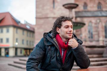 Junger Mann sitzend auf einer Bank Urbano Locken City