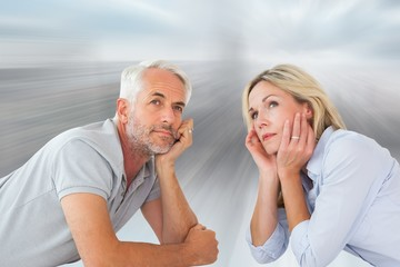 Composite image of thoughtful couple lying and looking up