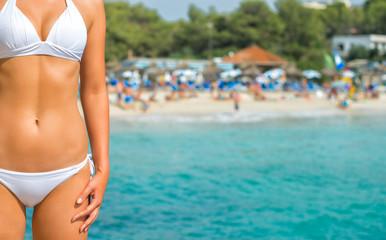 Part of suntanned woman body against beach.