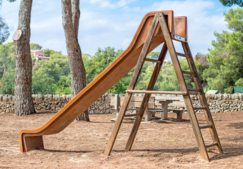 Wooden children's slide in the forest.