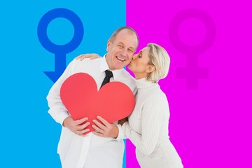 Older affectionate couple holding red heart shape