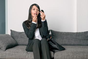 Attraktive Geschäftsfrau trägt roten Lippenstift auf