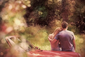 Loving couple admiring nature while leaning on their cabriolet