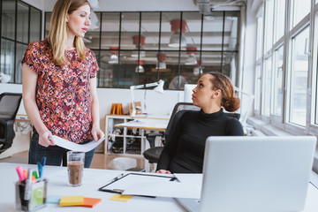 Woman discussing work with colleague at office