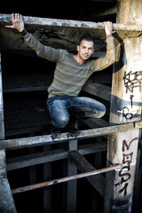 Handsome smiling young man in abandoned industrial site