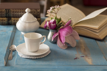 A pretty coffee cup and sugar bowl on old wooden table