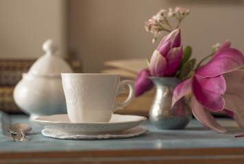 A tea cup with sugar bowl on old wooden table.