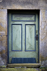 Old green door in a stone frame