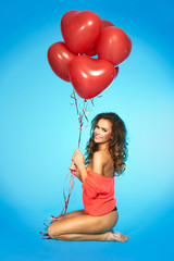 Smiling, beautiful woman with balloons over blue background