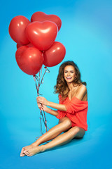 Young beautiful woman holding red balloons on blue background