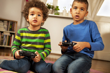 Mixed race boys playing video games at home.