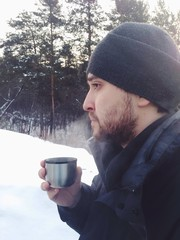 young man drinking tea and looking into the distance