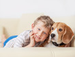 canvas print picture - Happy boy with his dog lying on sofa
