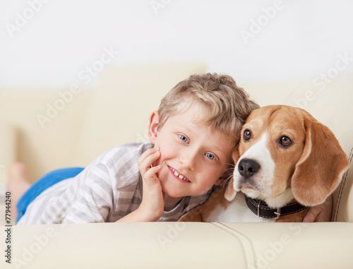 canvas print picture Happy boy with his dog lying on sofa