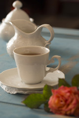Pretty coffee cup, creamer, sugar bowl on old wooden table.