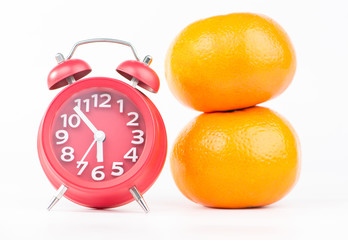 Red alarm clock and orange fruits show food and healthy time