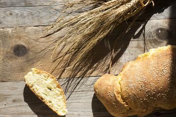 Sfondo con luce naturale di pane e spighe di grano su legno