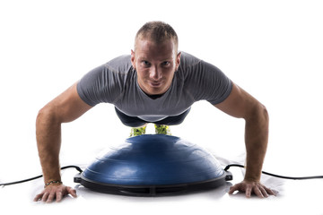 Attractive athletic young man working out with balance board