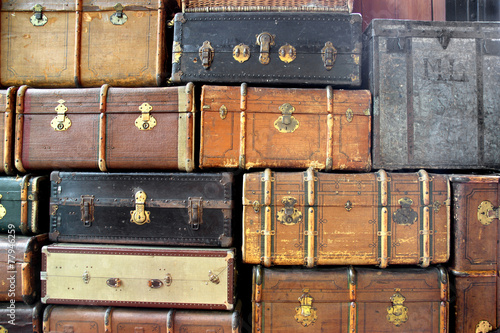background with large stack of antique suitcases - 77946259