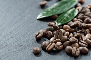 roasted coffee beans and leaves on a dark background